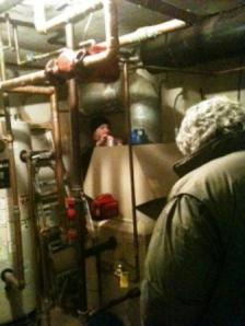 Plumber repairing flue pipe (background). Property Manager (foreground).